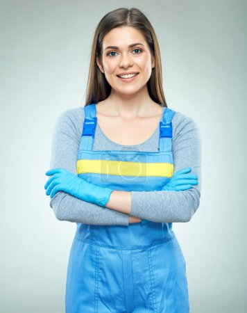 Smiling woman builder wearing overalls standing with crossed arms on grey background