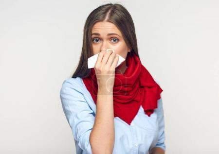 sick flu woman with red scarf on neck using paper tissue