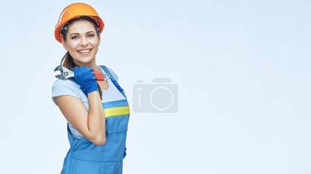smiling woman builder in safety helmet holding wrench on light background