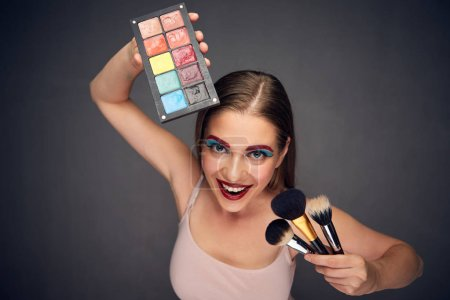 makeup master woman holding brushes and makeup palette on grey background, close-up