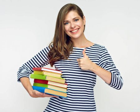 woman student holding pile of book and showing thumb up