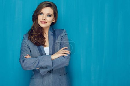 Smiling woman suit dressed standing with crossed arms