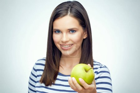 Photo for Girl smile with teeth and toothy braces holding green apple. Isolated portrait. - Royalty Free Image