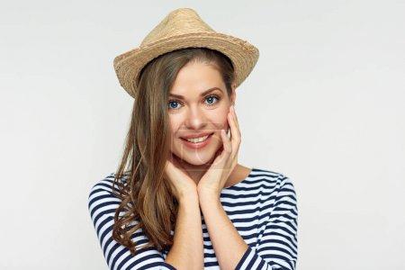 Foto de Retrato de mujer sonriente con sombrero y camisa a rayas mirando a la cámara y tocando mejillas - Imagen libre de derechos