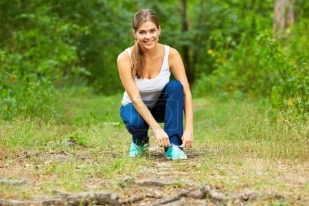 young woman runner tying trainer laces on  footpath in wood