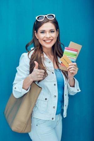 Photo pour Femme souriante en lunettes de soleil tenant billet et passeport avec carte de crédit sur fond bleu - image libre de droit