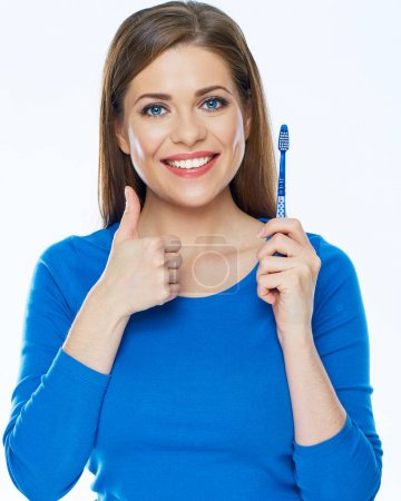 Smiling woman with healthy teeth holding toothy brush show thum