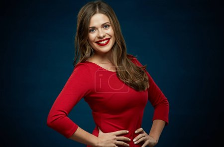 Photo for Portrait of smiling woman wearing red dress posing on dark background - Royalty Free Image