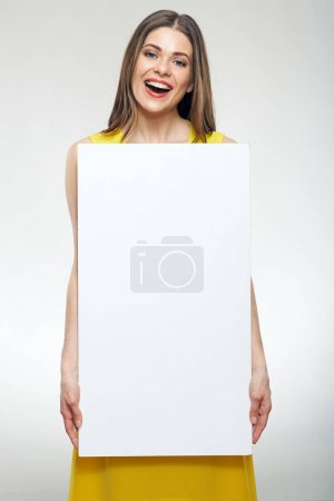 smiling woman in yellow dress holding white empty advertising board