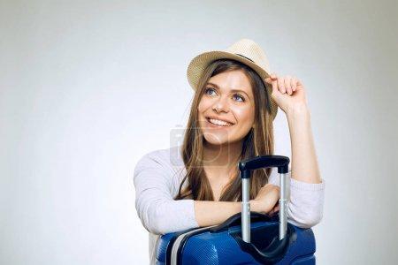 Photo pour Femme souriante voyageur tenant la carte de crédit et s'appuyant sur la valise - image libre de droit