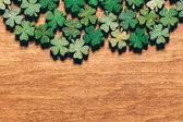 Wooden green shamrocks laying on the wooden floor. St. Patrick's Day. Symbol of luck.