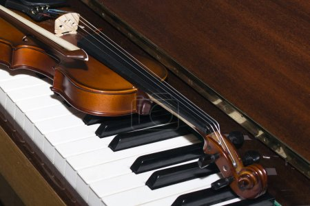 Very old violin lying on the piano