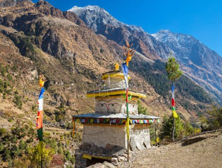 Stupa with Buddha wisdom eyes and prayer colorful flags in Hymalayas mountains.