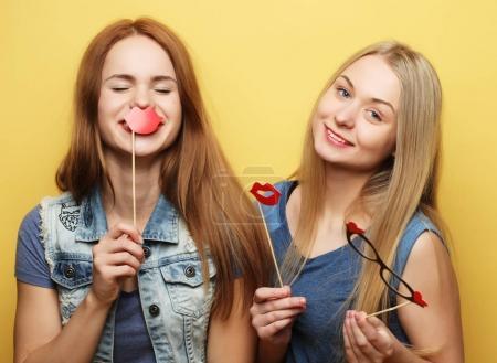 Photo pour Deux filles élégantes hipster sexy meilleures amies prêts pour le parti, sur fond jaune - image libre de droit