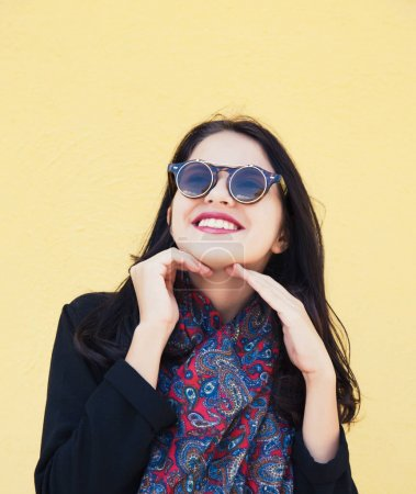 Photo for Young female fashion model with sunglasses shot over yellow fackground - Royalty Free Image
