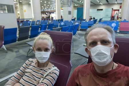 Photo for Woman and man in medical protective mask in an empty airport hall during a coronavirus pandemic. - Royalty Free Image