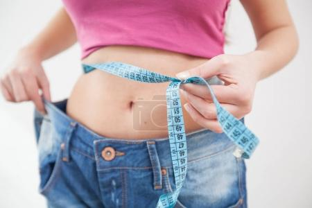 Photo for Slim Female measuring her thin waist with a tape measure,  woman in jeans, Unrecognizable person - Royalty Free Image