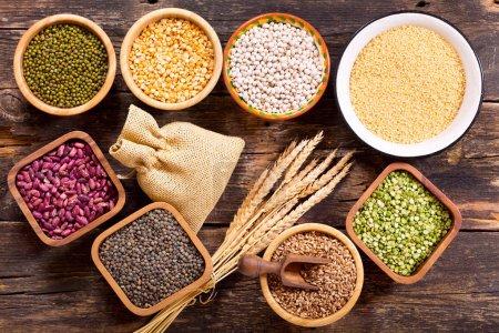 Photo pour Diverses céréales, graines, haricots et grains sur table en bois, vue de dessus - image libre de droit