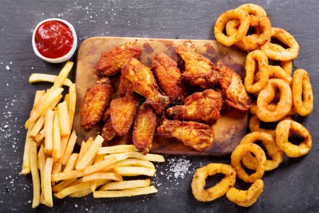 fast food meals : onion rings, french fries and fried chicken
