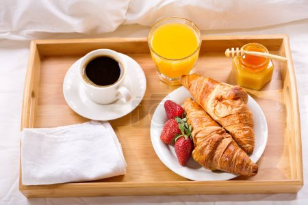 Photo for Breakfast tray in bed : coffee, croissants, juice and fresh strawberries - Royalty Free Image