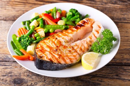 Photo for Plate of grilled salmon steak with vegetables on wooden table - Royalty Free Image