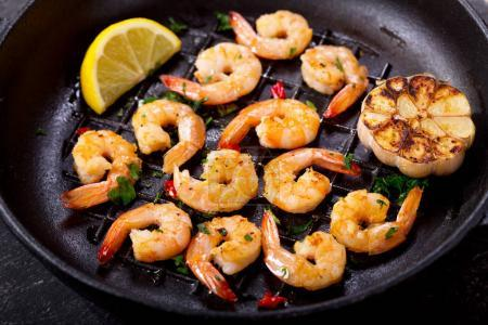 Photo for Pan of grilled shrimps on a dark table - Royalty Free Image