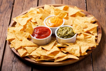 Photo for Mexican nachos corn chips with guacamole, salsa and cheese dip on wooden table - Royalty Free Image