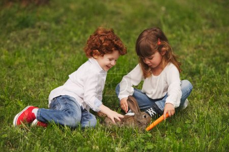 Photo for Little boy and girl playing with rabbit in park - Royalty Free Image