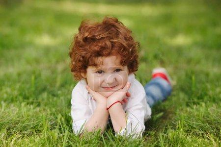 Photo pour Photo de petit garçon mignon couché sur l'herbe - image libre de droit