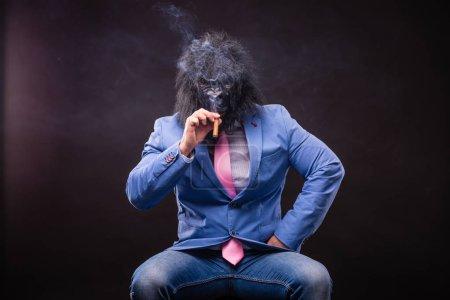 Photo pour Homme d'affaires portant le masque de gorille et fumeur de cigare - image libre de droit