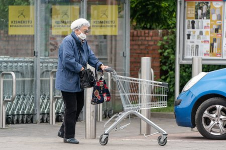 Photo for PECS - MAY 27 : Old woman go to shopping on the street  on 27 May 2020 in Pecs, Hungary. During coronavirus pandemic, everybody have to waering face mask - Royalty Free Image