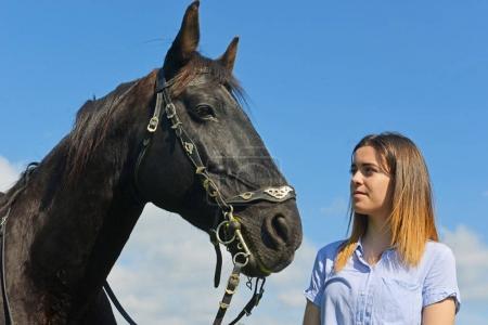 Photo pour Jeune fille d'équitation et son étalon noir dans la nature - image libre de droit