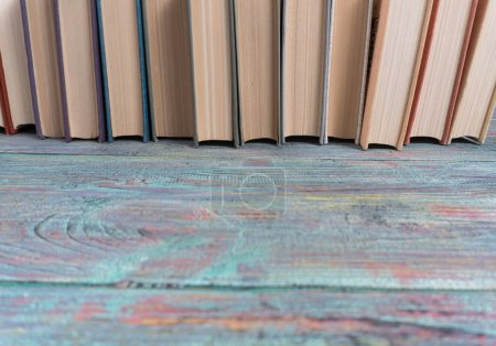 A lot of books on a colored wooden background with...