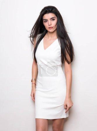 Photo pour Belle jeune femme avec de longs cheveux noirs portant une robe blanche - image libre de droit