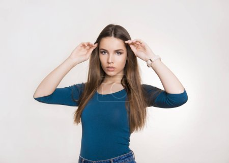 Photo for Beautiful young woman with long brown hair wearing wrist watch and posing in grey background with copy space - Royalty Free Image