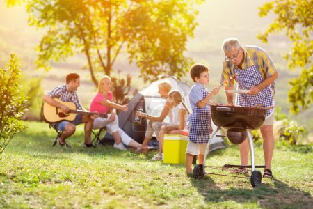 happy family grilling meat on a barbecue