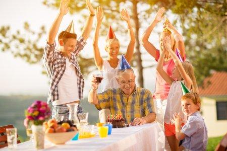 Photo pour Famille heureuse célébrer l'anniversaire du grand-père - image libre de droit
