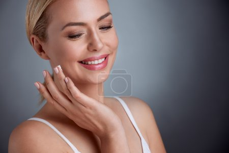 Nice middle aged woman  applying face cream