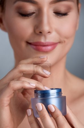 Smiling woman using cosmetic cream