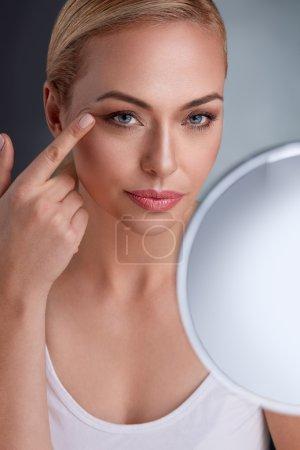 Beautiful woman with mirror