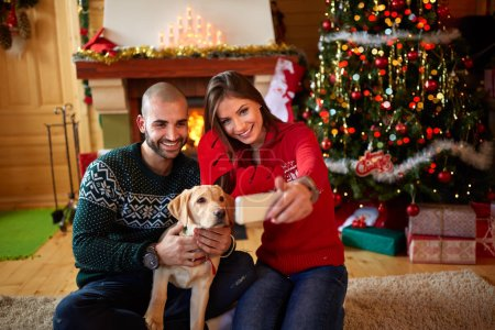 Selifie of couple with dog at Christmas