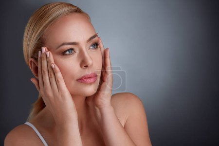 Woman tightening skin on face to make you look you...