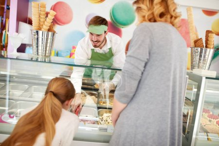 Vendor in confectionery serves girl with ice cream