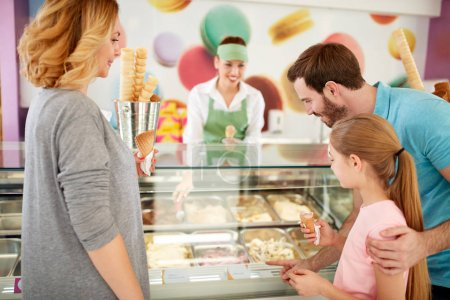 Girl with parents chooses flavors of ice cream