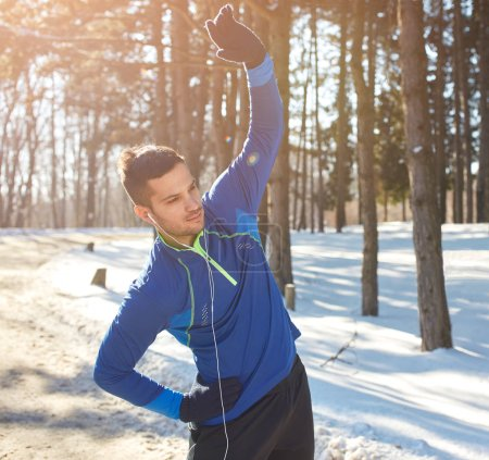 Male exercises in forest in winter