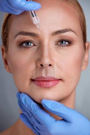 femme d'âge mûr reçoit injection cosmétique en front