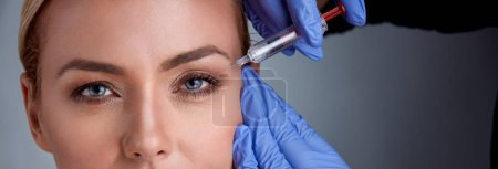 Cheerful middle age woman is getting botox procedure