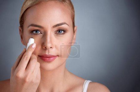 woman putting concealer under her eyes