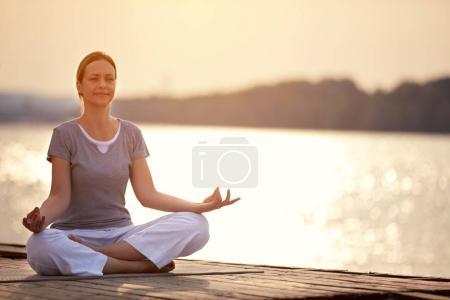 Photo pour Femme sur le quai, assis dans l'yoga posent et méditer - image libre de droit