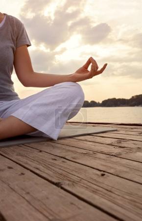 Photo pour Femelle, pratiquer l'yoga en posture de lotus sur le quai, concept - image libre de droit